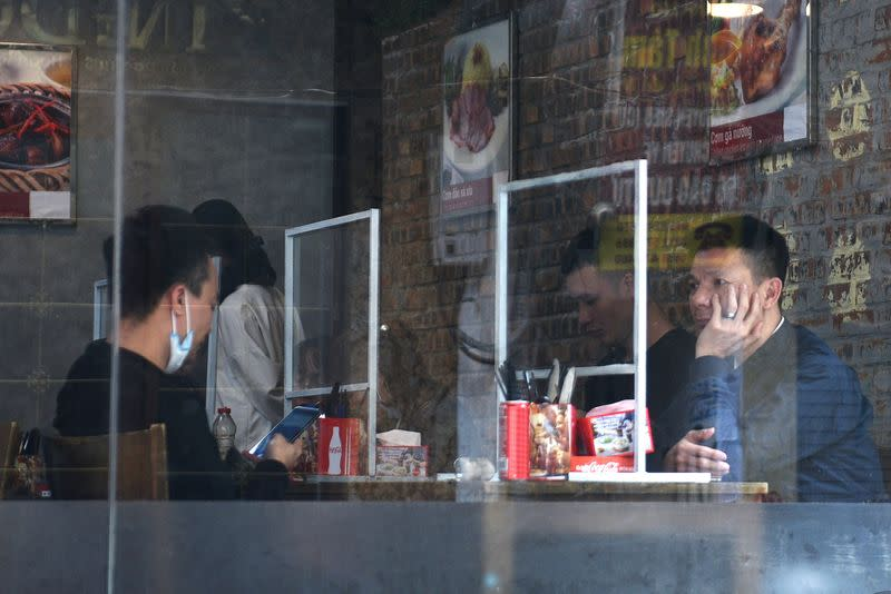 FILE PHOTO: People sit in a restaurant behind plastic dividers as a measure against the sread of the coronavirus disease (COVID-19) in Hanoi