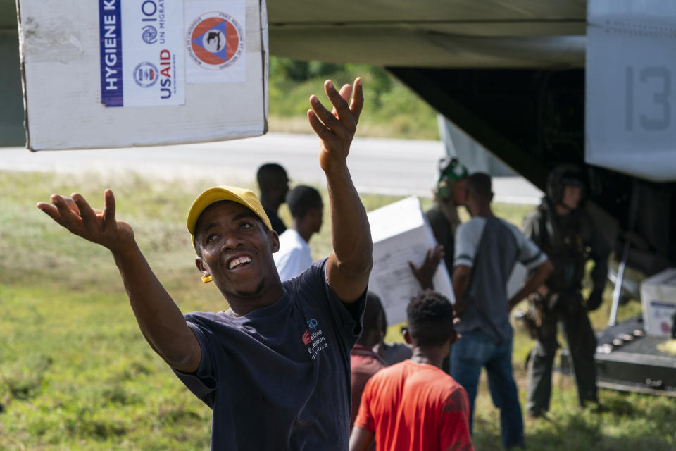 """A Haitan aid worker tosses a hygiene kit while unloading a VM-22 Osprey at Jeremie Airport, Saturday, Aug. 28, 2021, in Jeremie, Haiti. The VMM-266, """"Fighting Griffins,"""" from Marine Corps Air Station New River, from Jacksonville, N.C., are flying in support of Joint Task Force Haiti after a 7.2 magnitude earthquake on Aug. 22, caused heavy damage to the country. (AP Photo/Alex Brandon)"""