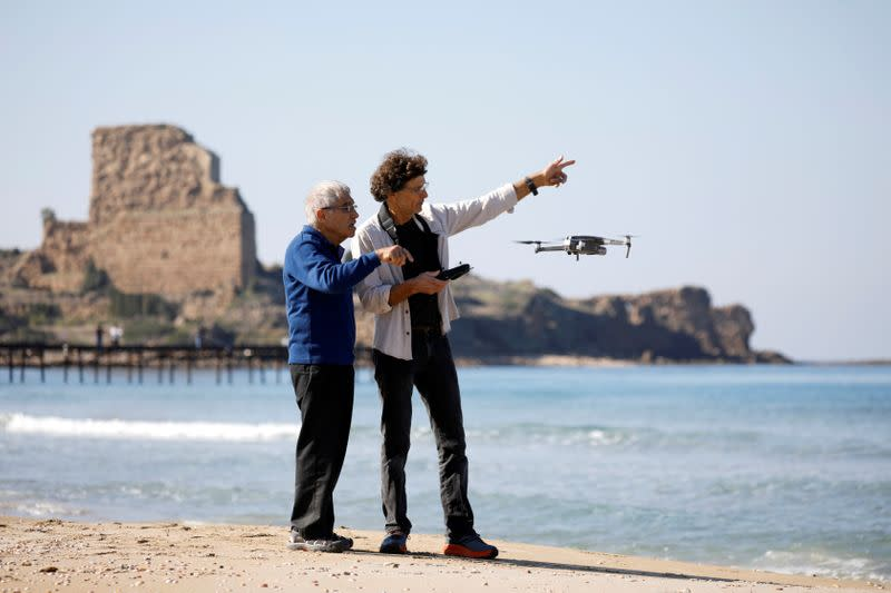 Israeli archaeologist Ehud Galili of the University of Haifa speaks to an Israeli photographer as they use a drone as part of their research work near Atlit, northern Israel