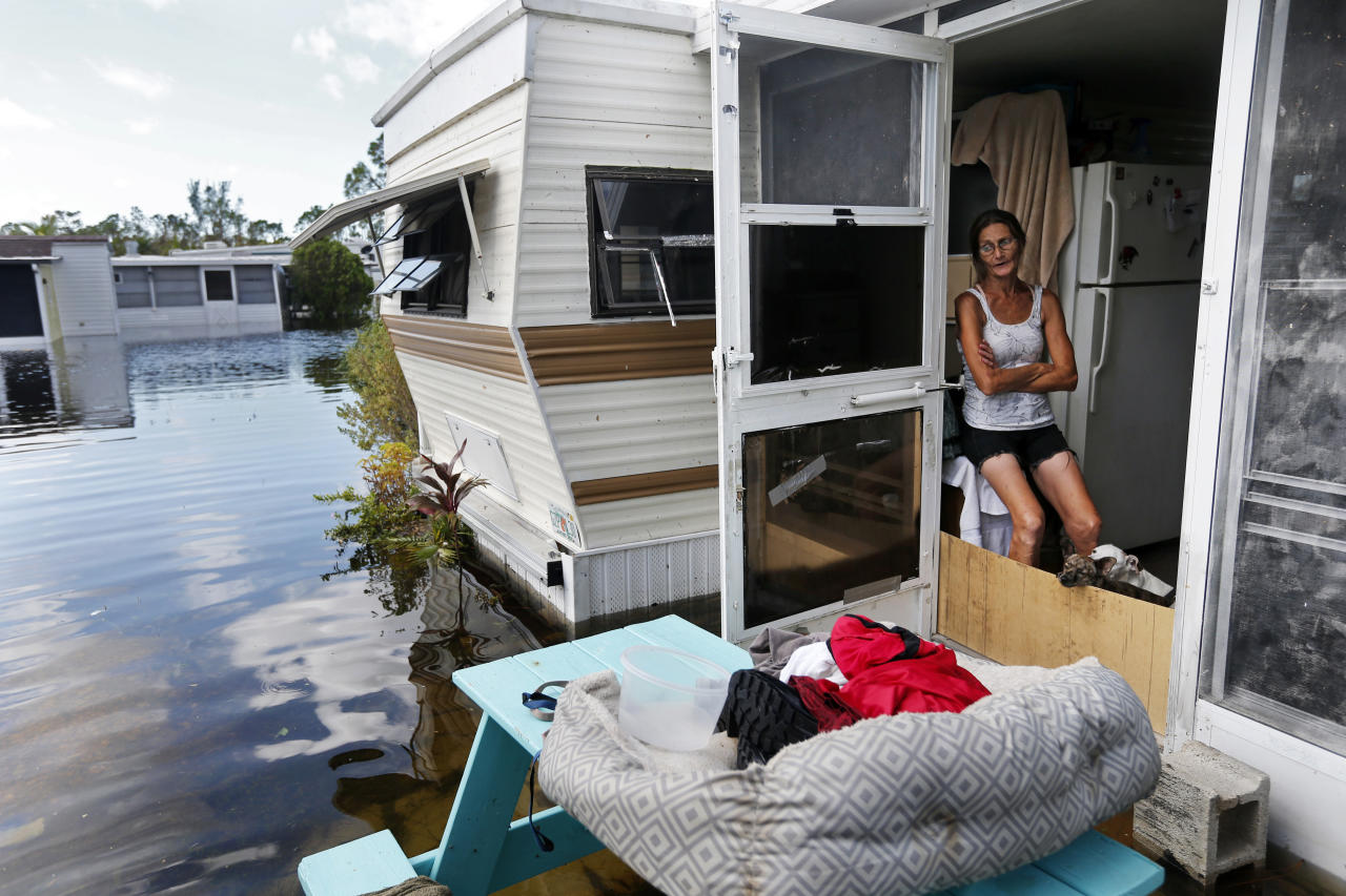<p>Cherie Ethier sits in her mobile home with her pets surrounded by floodwater, in the Marco Naples RV Resort in the aftermath of Hurricane Irma, in Naples, Fla., Sept. 12, 2017. (Photo: Gerald Herbert/AP) </p>