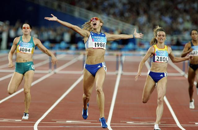 ATHENS - AUGUST 25: Fani Halkia of Greece crosses the finish line in first place in the women's 400 metre hurdle final, with Jana Pittman (left) of Australia finishing fifth and Ionela Tirlea-Manolache (r) of Romania finishing second on August 25, 2004 during the Athens 2004 Summer Olympic Games at the Olympic Stadium in the Sports Complex in Athens, Greece. (Photo by Stuart Hannagan/Getty Images)