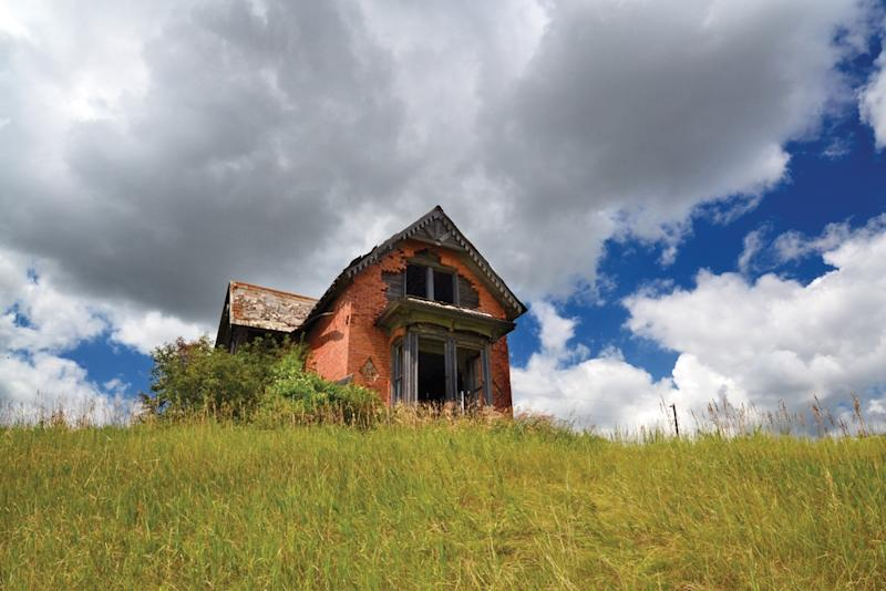 "This photo provided by Troy Larson shows an abandoned house in Sims, N.D., and is featured on the cover of the book ""Ghosts of North Dakota Volume 2,"" which documents ghost towns throughout the state. (AP Photo/Troy Larson)"