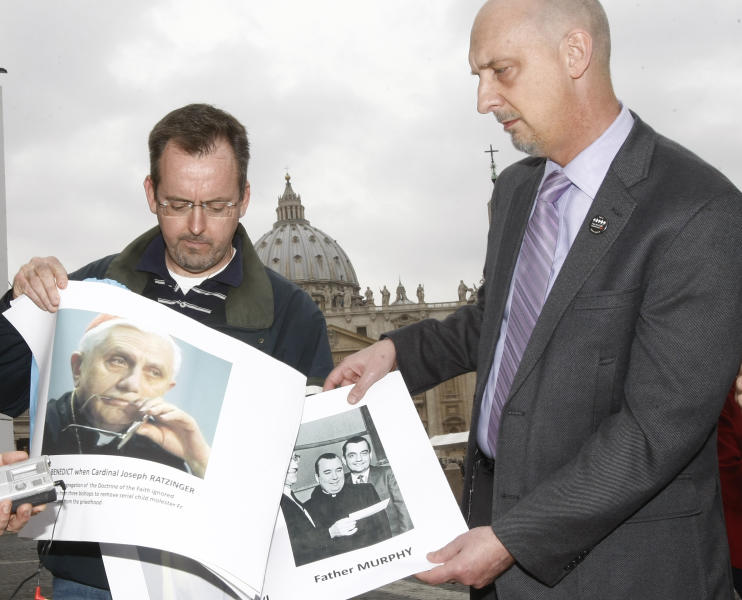 """FILE - In this Thursday, March 25, 2010 file photo, John Pilmaier from Milwaukee, left, and Peter Isely of SNAP (Survivors Network of those Abused by Priests) hold pictures of Cardinal Joseph Ratzinger, who became Pope Benedict XVI, left, and Father Lawrence Murphy during a news conference in front of the Vatican. SNAP members denounced Benedict's handling of the case that involved father Murphy, who died in 1998, accused of molesting some 200 deaf boys as he worked at the former St. John's School for the Deaf in St. Francis from 1950 to 1975. While many Americans are riveted by the Penn State sex abuse trial, it has been particularly wrenching - and sometimes heartening - for those who were themselves victims of abuse in their youth. Pilmaier says he reached a financial settlement with the Milwaukee Archdiocese, but was prevented by Wisconsin's statute of limitations from taking the priest to court. """"It's heartening for me to see them testify and hold the person accountable - a lot of us weren't able to do that,"""" Pilmaier said. (AP Photo/Pier Paolo Cito)"""