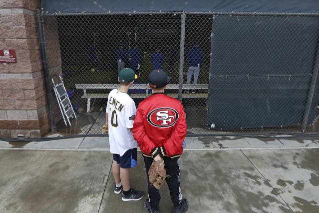 Jackson Starbuck, left, and Raymond Nylen, both 12 and from Fresno, Calif., watch Texas Rangers at batting practice after the cancellation of a spring training baseball game on the adjacent field between the Kansas City Royals and the Seattle Mariners, Thursday, March 12, 2020, in Surprise, Ariz. Major League Baseball is delaying the start of its season by at least two weeks because of the coronavirus outbreak and has suspended the rest of its spring training game schedule. (AP Photo/Elaine Thompson)