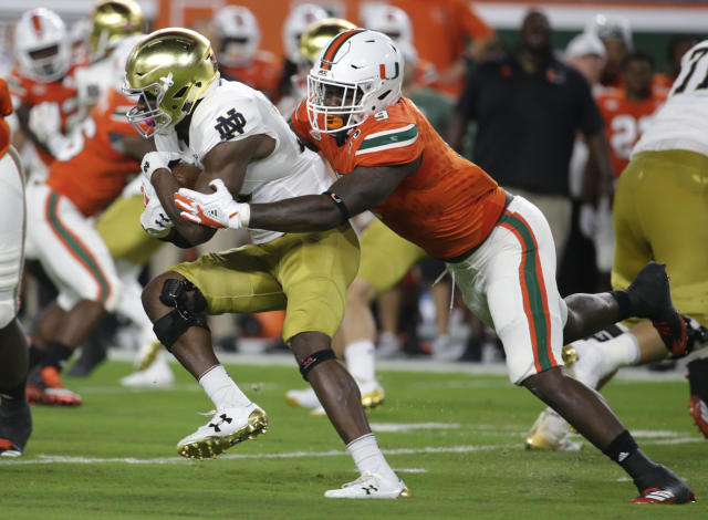 "Notre Dame running back <a class=""link rapid-noclick-resp"" href=""/ncaaf/players/257306/"" data-ylk=""slk:Josh Adams"">Josh Adams</a>, left, is tackled by Miami defensive lineman Chad Thomas during the first half of an NCAA college football game, Saturday, Nov. 11, 2017, in Miami Gardens, Fla. (AP Photo/Lynne Sladky)"