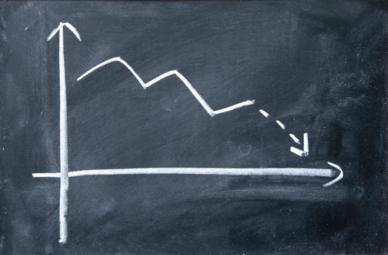 Black and white chalkboard chart showing a downward-trending arrow.