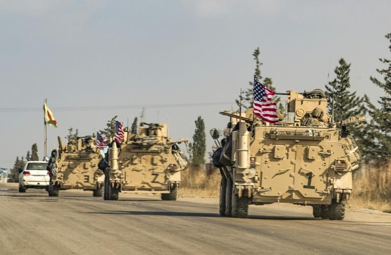A convoy of US troops drives through the Kurdish-majority city of Qamishli in northeast Syria