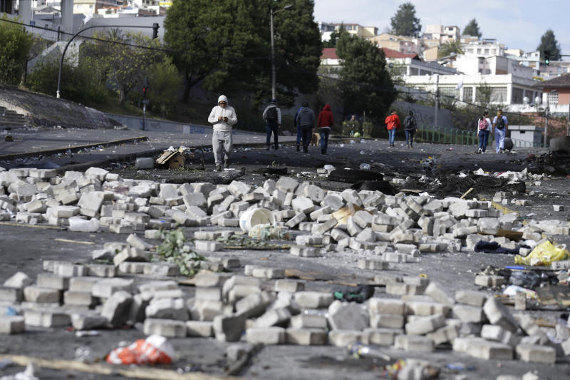Pedestrians walk through the debris of barricades set by anti-government demonstrators the day after violent protests in Quito, Ecuador, Sunday, Oct. 13, 2019. President Lenin Moreno ordered the army onto the streets of Ecuador's capital Saturday after a week and a half of protests over fuel prices devolved into violent incidents. (AP Photo/Fernando Vergara)