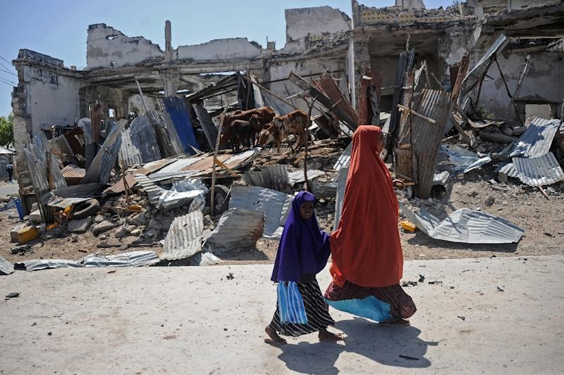 Local residents walk past the scene of a deadly December 22, 2018 car bomb attack in the Somali capital Mogadishu claimed by the jihadist group Shabaab