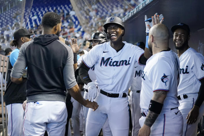 Miami Marlins' Jesus Sanchez, center, celebrates in the dugout after hitting a two-run home run during the first inning of a baseball game against the Cincinnati Reds, Sunday, Aug. 29, 2021, in Miami. (AP Photo/Lynne Sladky)