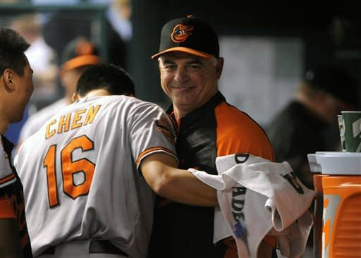 Baltimore Orioles starting pitcher Wei-Yin Chen (16), of Taiwan, hugs pitching coach Rick Adair following the fourth inning of a baseball game against the Tampa Bay Rays, Saturday, Aug. 4, 2012, in St. Petersburg, Fla. (AP Photo/Brian Blanco)