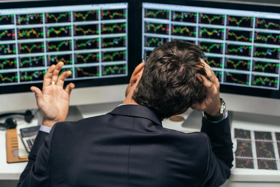 A visibly frustrated investor holding the top of his head while looking at dozens of stock charts on two computer monitors.