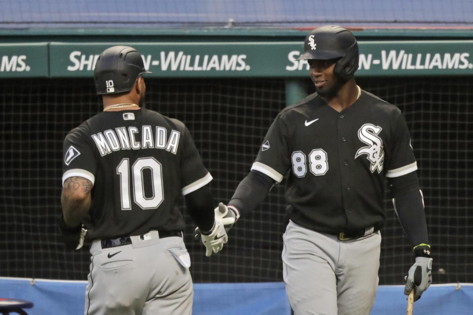 Chicago White Sox's Yoan Moncada (10) is congratulated by Luis Robert (88) after Moncada scored in the ninth inning in a baseball game against the Cleveland Indians, Wednesday, July 29, 2020, in Cleveland. (AP Photo/Tony Dejak)