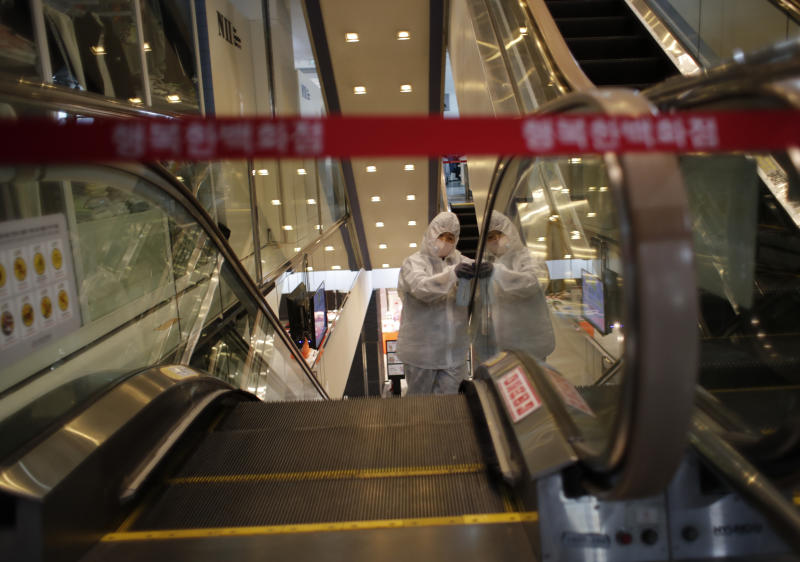 A worker wearing protective gear sprays disinfectant as a precaution against the new coronavirus at a department store in Seoul, South Korea, Monday, March 2, 2020. South Korea has the world's second-highest cases. (AP Photo/Lee Jin-man)
