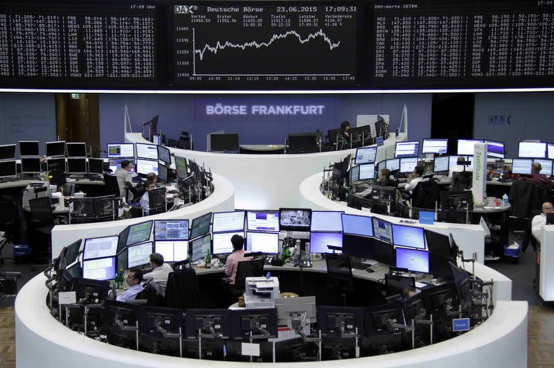 Traders work at their screens in front of the German share price index DAX board at the stock exchange in Frankfurt