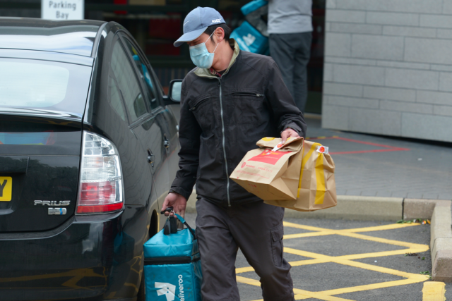 A delivery driver takes bags of McDonald's out to customers in Chelmsford, Essex. (PA)