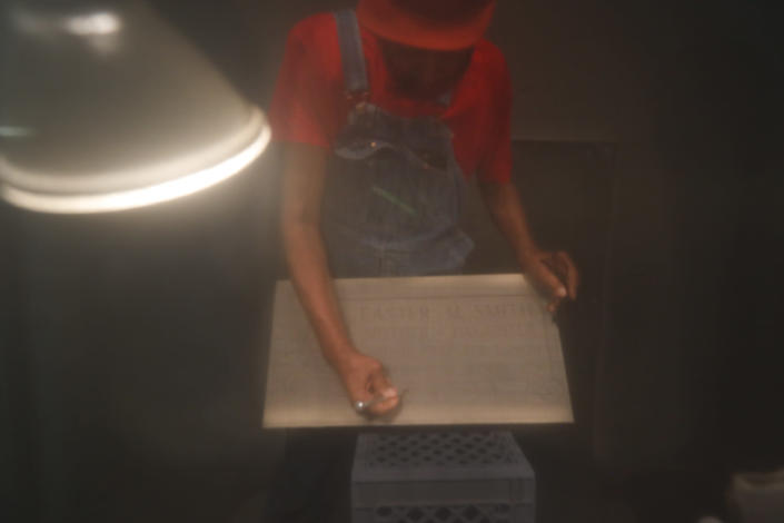 FILE - In this May 28, 2020, file photo, seen through plexiglass, Hosea Knox checks the precision of a sandblasted cut on the design of a new granite tombstone at his shop on Chicago's South Side. Knox, 82, died on Sept. 5, 2021, after serving the predominately Black community in their time of need for more than 33 years. (AP Photo/Charles Rex Arbogast, File)