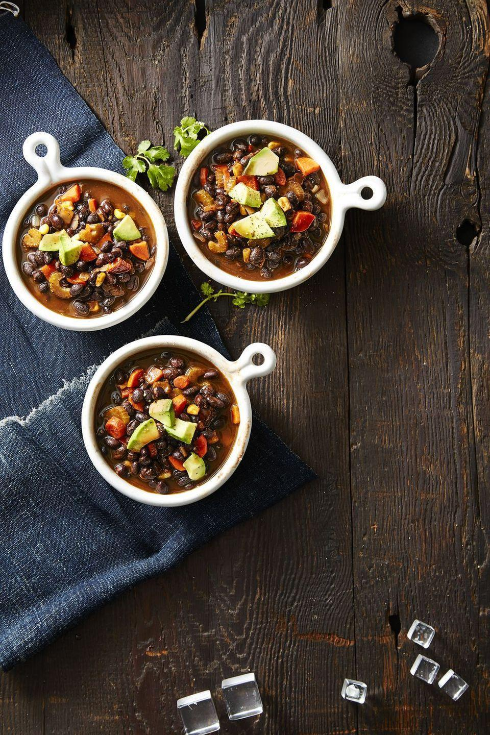 """<p>This healthy soup recipe may technically count as vegan but it's sure to fill you up. </p><p><em><a href=""""https://www.goodhousekeeping.com/food-recipes/healthy/a42397/smoky-vegan-black-bean-soup-recipe/"""" rel=""""nofollow noopener"""" target=""""_blank"""" data-ylk=""""slk:Get the recipe for Smoky Vegan Black Bean Soup »"""" class=""""link rapid-noclick-resp"""">Get the recipe for Smoky Vegan Black Bean Soup »</a></em></p>"""