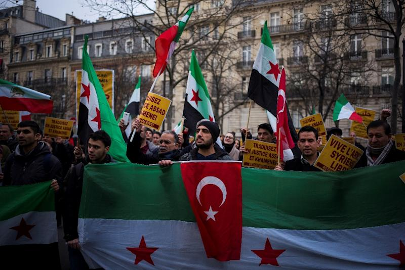 Syrian demonstrators in Paris protest near the Iranian embassy against Iranian involvement in the siege of Aleppo (AFP Photo/MARTIN BUREAU)