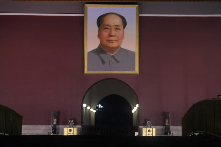 Chinese paramilitary policemen put on sunglasses while on duty, as spot lights light up Tiananmen Gate with its iconic portrait of late Chinese leader Mao Zedong in Beijing on Thursday, July 15, 2021. (AP Photo/Ng Han Guan)