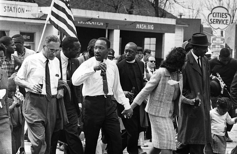 March 1965: Martin Luther King (1929 - 1968) and his wife Coretta Scott King lead a civil rights march from Selma, Alabama, to the state capital in Montgomery. On the left (holding bottle) is American diplomat Ralph Bunche (1904 - 1971). (Photo by William Lovelace/Express/Getty Images)
