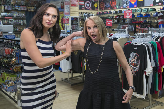<p>Yahoo Global News Anchor Katie Couric flexes her muscles with the assistance of actress Gal Gadot at the Midtown Comics in New York City. (Gordon Donovan/Yahoo News) </p>