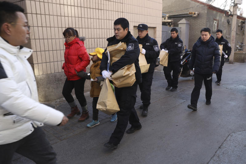 A woman walks away with a child as they leave the Beijing No. 1 Affiliated Elementary School of Xuanwu Normal School near crime scene investigators as they carrying evidence bags in Beijing China Tuesday Jan. 8 2019. A male attacker injured 20 childre