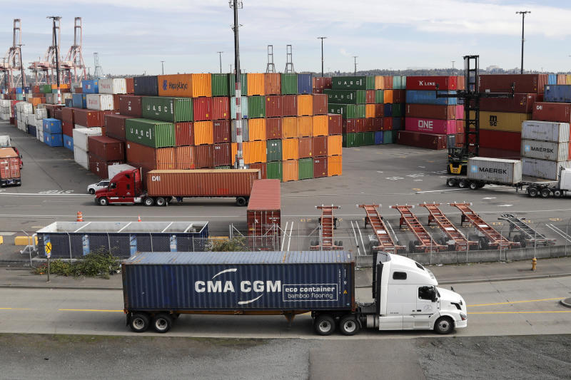 FILE - In this Oct. 2, 2019, file photo trucks hauling shipping containers drive near containers stacked five-high at a terminal on Harbor Island in Seattle. US and China are trying to finalize a modest trade agreement to deescalate a trade war that has rattled financial markets and hobbled global economic growth. (AP Photo/Elaine Thompson, File)