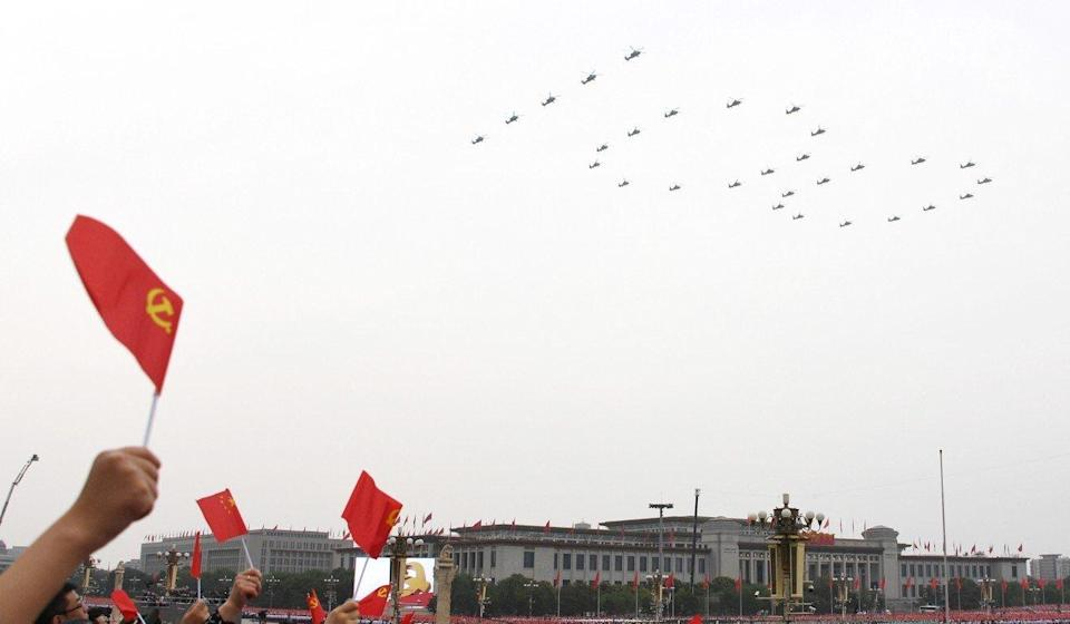 """Helicopters fly over Tiananmen Square in the """"100"""" formation. Phoot: Xinhua"""