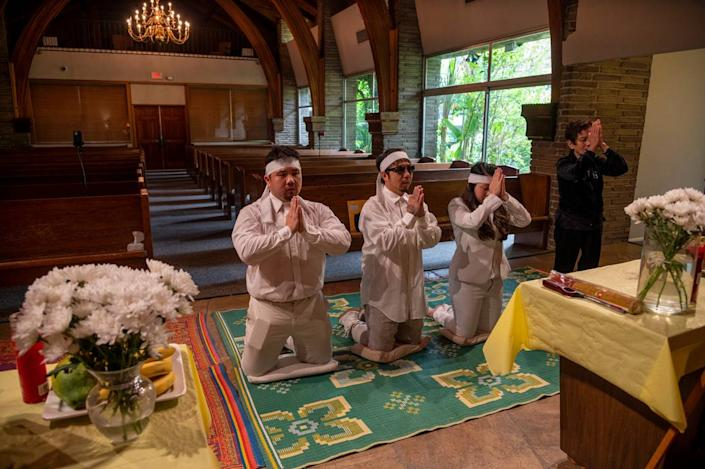 At Dung Tan Nguyen's funeral, family members, from left, Michael Chambon, Bao Nguyen, Trang Nguyen and Kim Anh Dinh, chant a Buddhist prayer, on Wednesday, May 6, 2020, during a service that would have been full of family and community members if it wasn't for the safety precautions put in place to protect against the coronavirus.