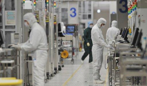 This file photo shows employees of Japan's microprocessor maker Renesas Electronics working at the company's Naka wafer factory in Hitachinaka, Ibaraki prefecture, in 2011. Renesas plans to cut 6,000 jobs, or about 15 percent of its workforce, as it struggles to turn a profit, Japan's biggest daily reported on Tuesday