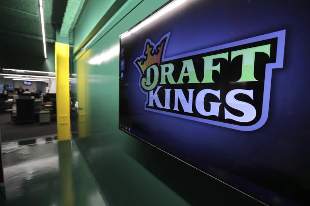 """FILE - In this May 2, 2019, file photo, the DraftKings logo is displayed at the sports betting company headquarters in Boston. Sports gambling giant DraftKings won't give a former """"Bachelor"""" contestant the $1 million prize for winning an online fantasy football contest after she and her husband were accused of cheating.Jade Roper-Tolbert beat more than 100,000 entries to take the top prize, but some in the fantasy sports community were quick to allege she coordinated with her husband, Tanner Tolbert, to submit more than the maximum 150 entries. Roper-Tolbert was no longer listed as the winner Saturday. A DraftKings statement says the company decided to update the standings for several contests and did not elaborate. (AP Photo/Charles Krupa, File)"""
