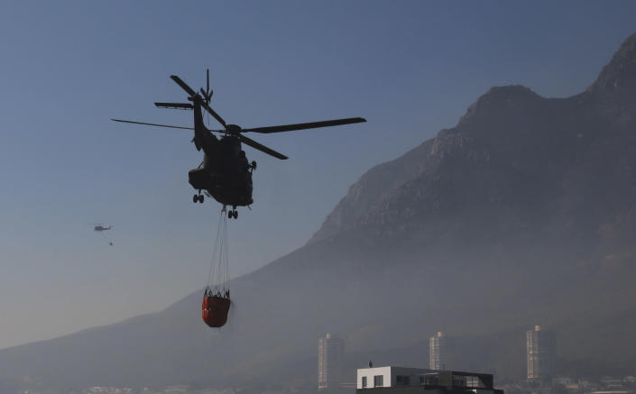 Water bombing helicopters hover by the slopes of Cape Town's, Table Mountain slopes, in South Africa, Tuesday, April 20, 2021. Fire crews worked for a third day to extinguish a wildfire as the city came to terms with the damage caused by what officials have described as one of the area's worst blazes in years. (AP Photo/Nardus Engelbrecht)