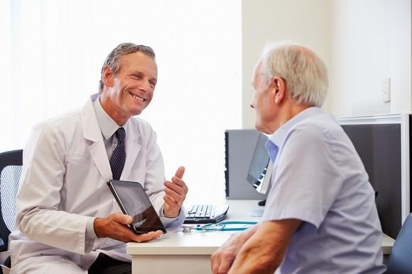 A doctor using a tablet to deliver positive test results to an elderly patient.