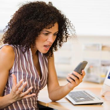 Angry-businesswoman-holding-phone-at-desk_web