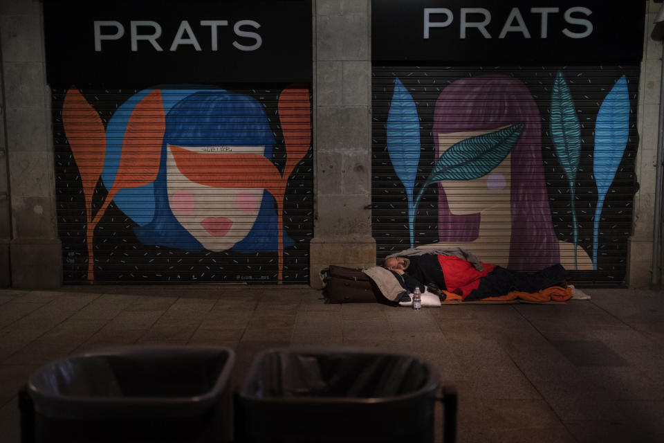 A homeless man sleeps on a street in downtown Barcelona, Spain, late Friday, March 5, 2021. According to reports, poverty have increased considerably in the last months as Spain has been in lockdown to fight the coronavirus pandemic. (AP Photo/Emilio Morenatti)