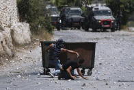 Palestinians clash with Israeli security forces following the funeral of Mohammed al-Alami, 12, in the village of Beit Ummar, near the West Bank city of Hebron, Thursday, July 29, 2021. Villagers say the boy was fatally shot by Israeli troops while traveling with his father in a car. The Israeli military has launched an investigation into the shooting. (AP Photo/Majdi Mohammed)