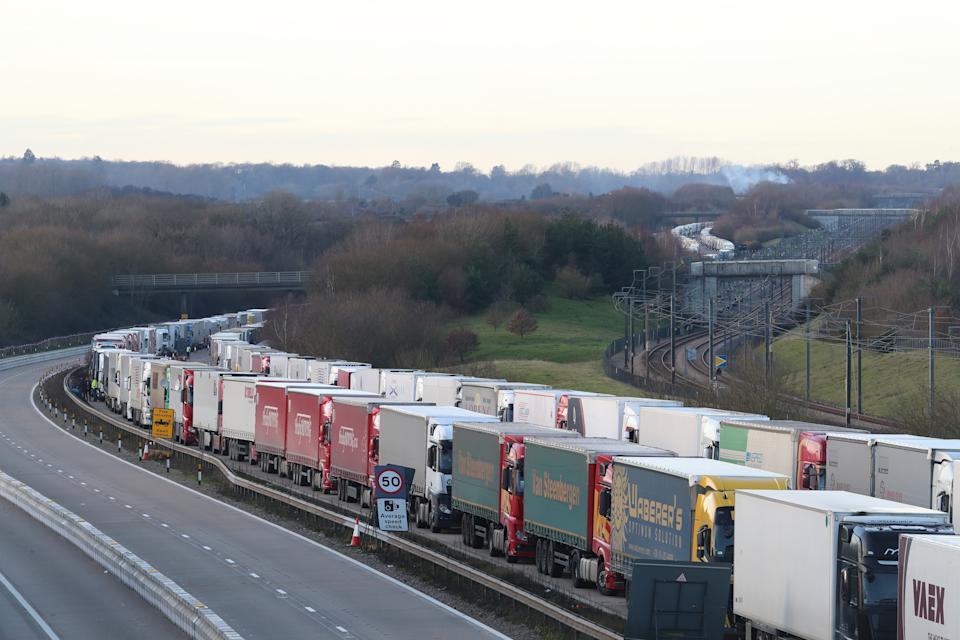 Freight lorries lined up on the M20 near Ashford, Kent, where hundreds of travellers are spending Christmas Day as they wait to resume their journey to the Port of Dover and across The Channel now that the borders with France have reopened. (Photo by Gareth Fuller/PA Images via Getty Images)