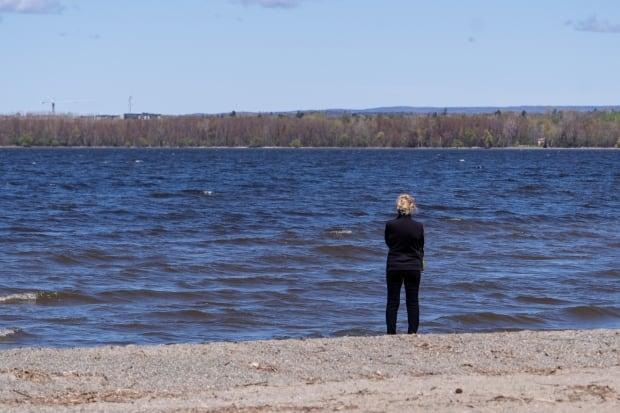 A person stands along the shore of the Ottawa River in Britannia Park on a sunny spring day on May 12.