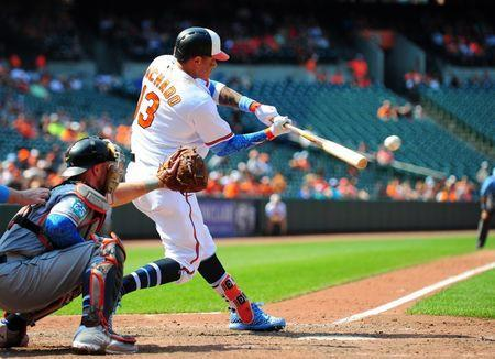 Jun 17, 2018; Baltimore, MD, USA; Baltimore Orioles shortstop Manny Machado (13) hits an RBI single in the eighth inning against the Miami Marlins at Oriole Park at Camden Yards. Mandatory Credit: Evan Habeeb-USA TODAY Sports