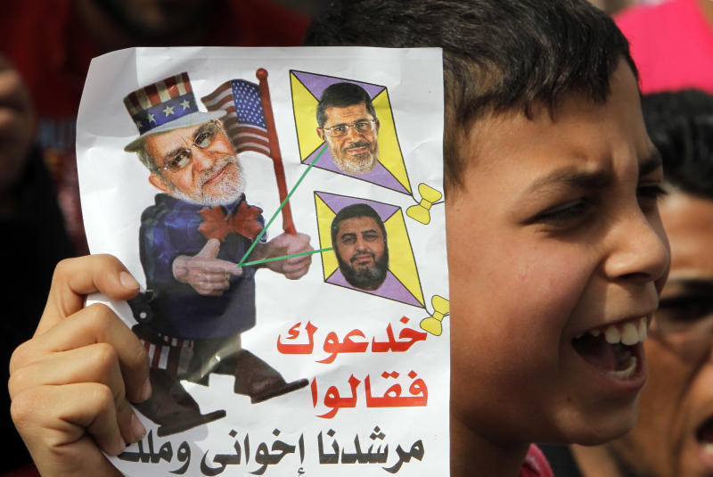 "An Egyptian boy holds a cartoon criticizing Muslim Brotherhood Supreme Leader Mohammed Badie, left, Egyptian President Mohammed Morsi, top right, and Muslim Brotherhood deputy leader Khairat el-Shater during anti-Muslim brotherhood protest, in Cairo, Egypt, Friday, March 15, 2013. Hundreds of supporters of the military gathered Friday to reject the Muslim Brotherhood and President Mohammed Morsi's rule calling for the military to return to power. Arabic reads, "" they lie to you and said our Brotherhood Leader is a king."" (AP Photo/Amr Nabil)"