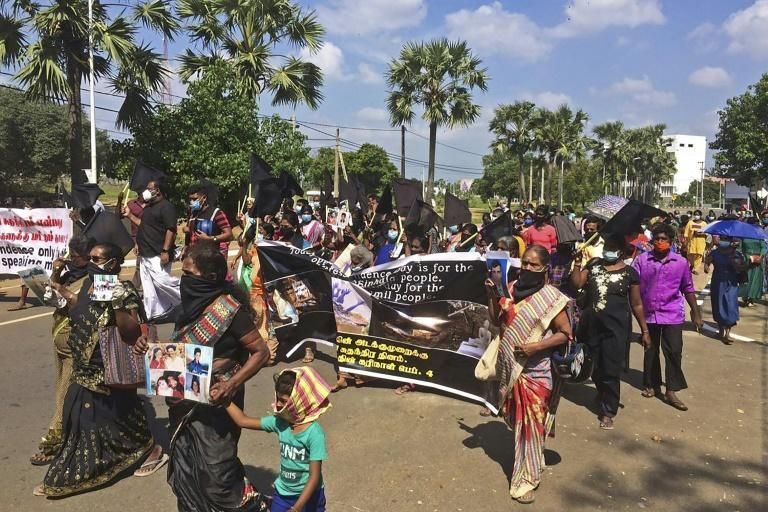 Demonstrators carry black flags and pictures of missing Tamils during a protest march in Sri Lanka's northern town of Kilinochchi