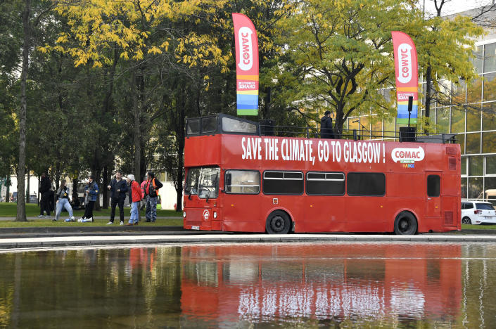 Protestors march alongside a bus during a climate demonstration in Brussels, Sunday, Oct. 10, 2021. Some 80 organizations are joining in a climate march through Brussels to demand change and push politicians to effective action in Glasgow later this month.(AP Photo/Geert Vanden Wijngaert)