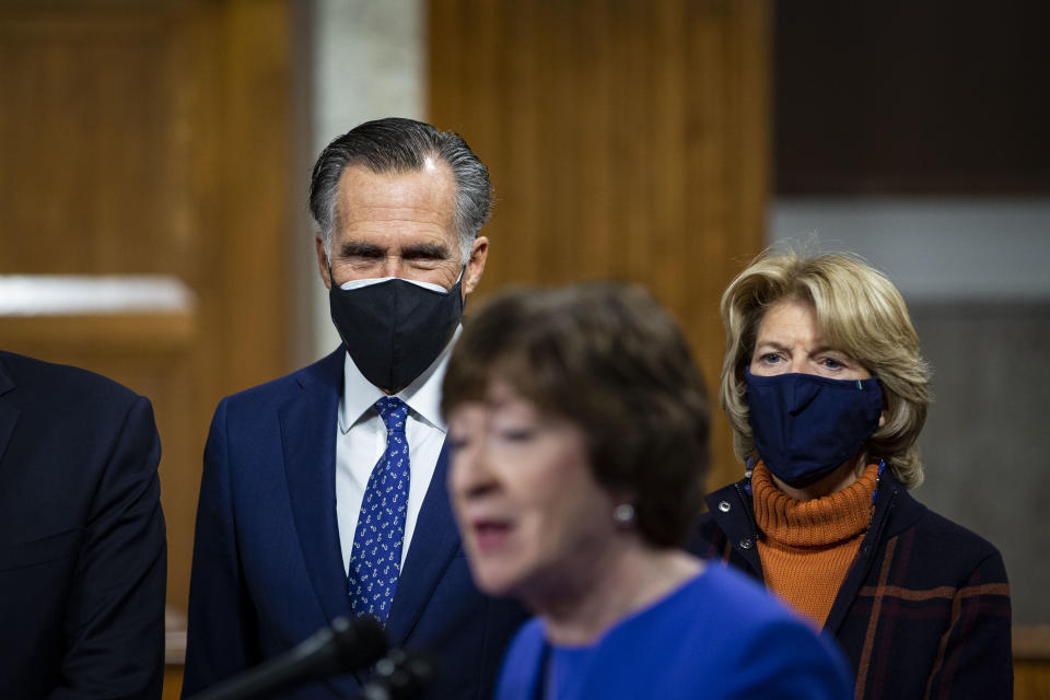 WASHINGTON, DC - DECEMBER 14: Senator Mitt Romney, a Republican from Utah, and Senator Lisa Murkowski, a Republican from Alaska, listen as Senator Susan Collins, a Republican from Maine, speaks during a news conference with a bipartisan group of lawmakers as they announce a proposal for a Covid-19 relief bill on Capitol Hill, on Monday, December 14, 2020 in Washington, DC. Lawmakers from both chambers released a $908 billion package Monday, split into two bills.(Photo by Al Drago for The Washington Post via Getty Images)