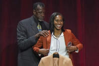 Harvey Catchings, left, helps daughter Tamika Catchings put on her Hall of Fame jacket at the 2020 Basketball Hall of Fame awards tip-off celebration and awards gala, Friday, May 14, 2021, in Uncasville, Conn. (AP Photo/Kathy Willens)