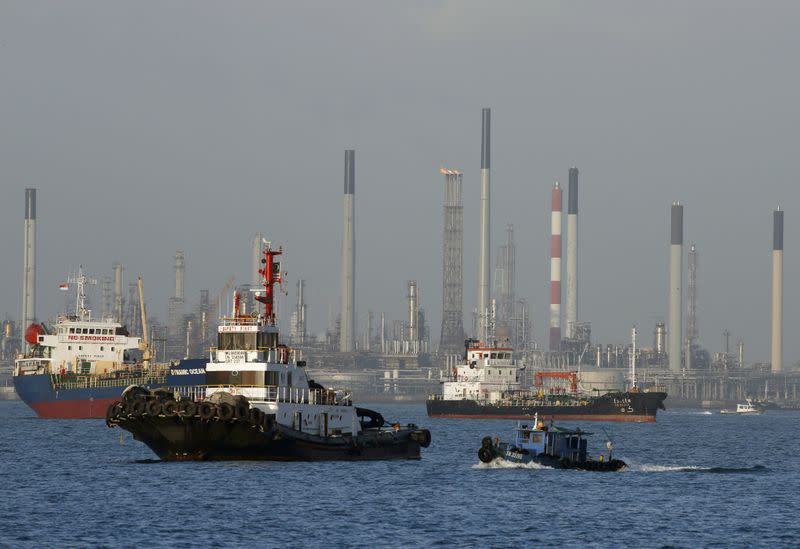 FILE PHOTO: Vessels pass an oil refinery in the waters off the southern coast of Singapore