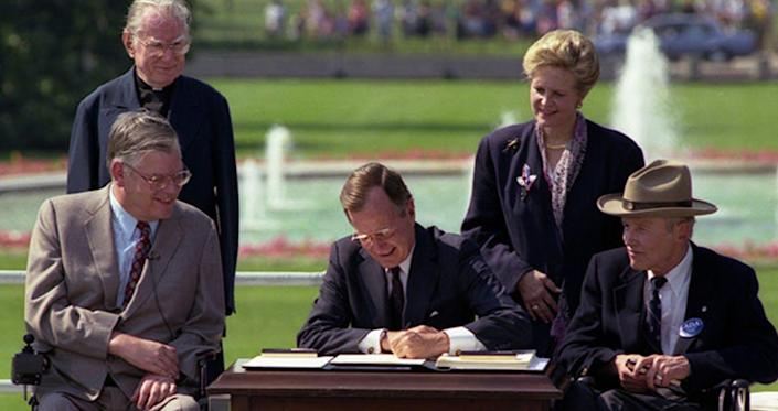 """<span class=""""caption"""">President George H.W. Bush signing the American Disabilities Act into law on July 26, 1990. </span> <span class=""""attribution""""><span class=""""source"""">George Bush Presidential Library and Museum/NARA</span></span>"""