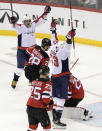 Washington Capitals right wing Tom Wilson (43) celebrates his goal with left wing Alex Ovechkin (8) as New Jersey Devils defenseman Damon Severson (28) and defenseman Mirco Mueller (25) react during the second period of an NHL hockey game Saturday, Feb. 22, 2020, in Newark, N.J. (AP Photo/Bill Kostroun)