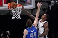 Dallas Mavericks forward Nicolo Melli (44) is unable to stop San Antonio Spurs guard Lonnie Walker IV (1) from dunking in the second half of an NBA basketball game in Dallas, Sunday, April 11, 2021. (AP Photo/Tony Gutierrez)