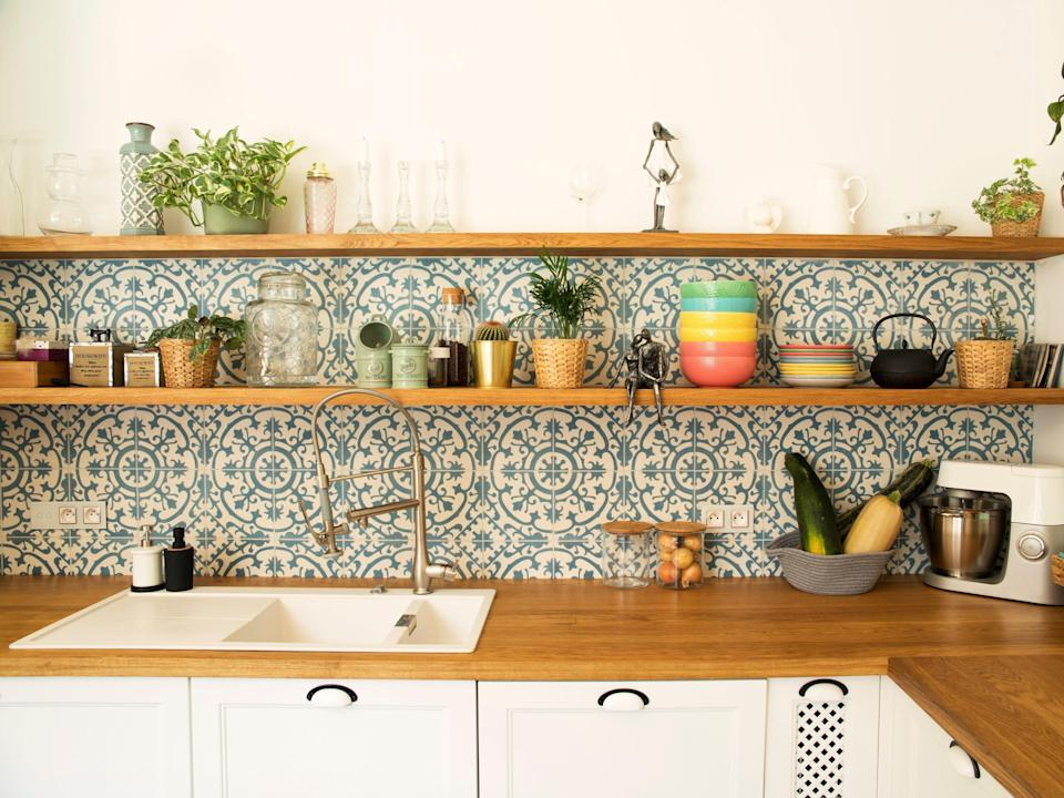 Stylish open space kitchen with accessories, plants and plates. Design interior of cozy kitchen. Mosaic backgrounds wall.